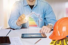 Engineer showing a model energy-efficient house . Engineer showing a model energy-efficient house on the tablet Royalty Free Stock Images