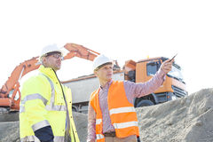 Engineer showing something to colleague while discussing at construction site against clear sky royalty free stock images