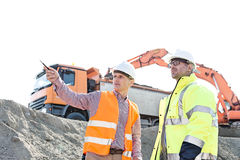 Engineer showing something to colleague while discussing at construction site against clear sky Stock Images