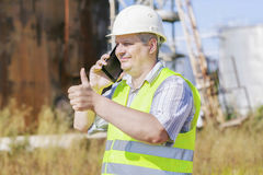 Engineer showing thumb up near to the tanks Stock Photography