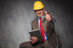 Engineer showing thumbs up while holding his tablet Stock Image