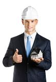 Engineer shows model house and thumbs up. Engineer in white hard hat shows small model house and thumbs up, isolated on white Stock Photo