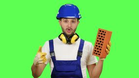 Engineer holds a brick in his hand and shows a thumbs up. Green screen stock video