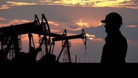 Engineer silhouette in front of oil pumps, red clouds sunset in background stock video