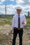 Engineer on site OK sign. Young engineer on site. He is holding blueprints in his hand and making an OK sign Royalty Free Stock Photos