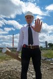 Engineer on site stop sign. Young engineer on site. He is holding blueprints in his hand and making a stop sign Royalty Free Stock Image