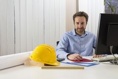 Engineer sitting in front of the computer in his office. Architecture and engineering: Engineer sitting in front of the computer in his office Stock Image