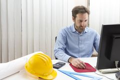 Engineer sitting in front of the computer in his office. Engineering: Engineer sitting in front of the computer in his office Stock Image