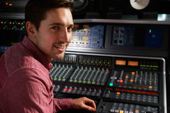 Engineer Sitting At Mixing Desk In Recording Studio Royalty Free Stock Photo