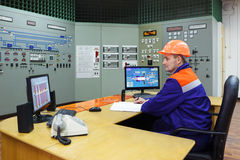 Engineer sitting writes in log. On main control panel of gas compressor station Royalty Free Stock Photos