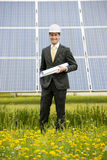 Engineer At Solar Power Station. Male engineer at solar power station holding blueprints Royalty Free Stock Photos