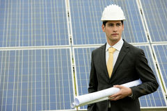 Engineer At Solar Power Station. Male engineer at solar power station holding blueprints Stock Photo