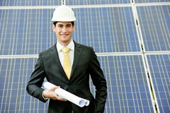 Engineer At Solar Power Station. Male engineer at solar power station holding blueprints Royalty Free Stock Photo