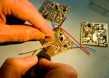 Engineer soldering wires to a circuit board. Royalty Free Stock Photos