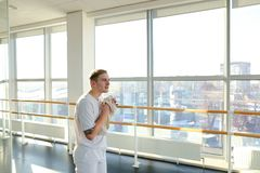 Engineer in sportswear rocking press in sport hall. Engineer rock press in sport hall, male want to perfect body. Barefoot tattooed man in white trousers lie on Stock Images