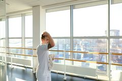 Engineer in sportswear rocking press in sport hall. Engineer rock press in sport hall, male want to perfect body. Barefoot tattooed man in white trousers lie on Royalty Free Stock Images