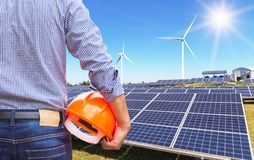 Engineer stand holding safety yellow helmet with solar cells and wind turbines generating electricity in hybrid power plant system. S station use renewable stock photo