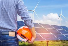 Engineer stand holding safety yellow helmet with solar cells and wind turbines generating electricity in hybrid power plant system Royalty Free Stock Images