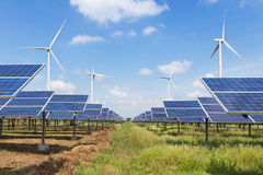 Engineer stand holding safety yellow helmet with solar cells and wind turbines generating electricity in power station site. Alternative renewable energy from royalty free stock image