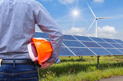 Engineer stand holding safety yellow helmet with solar cells and wind turbines generating electricity in power station Stock Photos