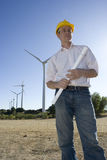 Engineer Standing in Front of Modern Wind Turbines Stock Image