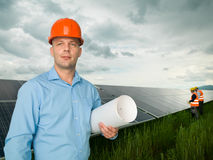 Engineer standing in front of solar panels Stock Photo