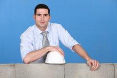 Engineer standing by wall. Engineer standing by a block wall Royalty Free Stock Photos