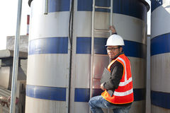Engineer and storage tank. Engineer standing beside tank oil refinery Royalty Free Stock Photography