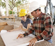 Engineer & Student Review Plan. An engineer and a female student going over blueprints on a construction site stock photo