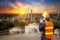 Engineer survey of oil refiner. And control worker from portable radio on storage tank in sunset background royalty free stock images