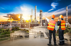 Engineer survey of oil refiner. And control worker from portable radio on storage tank in sunset background stock images