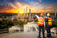 Engineer survey of oil refiner. And control worker from portable radio on storage tank in sunset background stock photography