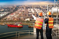 Engineer survey of oil refiner. On storage tank at riverside in sunset background stock photography