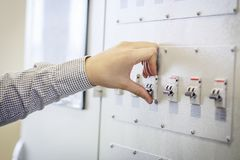 Engineer switches on circuit breaker in electric switchboard close-up royalty free stock images