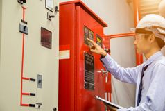 Engineer with tablet check red generator pump for water sprinkler piping and fire alarm control system. stock image