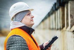 Engineer with tablet PC near the concrete wall Royalty Free Stock Images