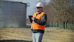 Engineer with tablet PC near oil tank stock footage