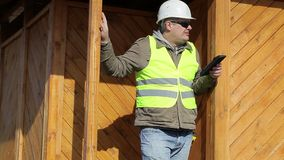 Engineer with tablet PC near wooden building stock video