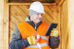 Engineer with tablet PC near wooden building Stock Images