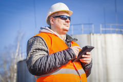 Engineer with tablet PC with oil tank in the background Stock Photos
