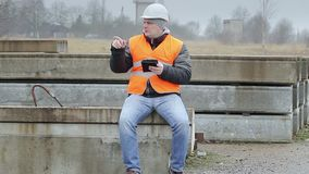 Engineer with tablet PC sitting on the concrete panels stock video