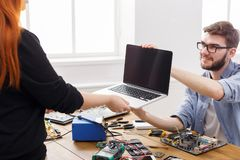Engineer taking broken laptop from client. Acceptance of damaged electronic device in repair service center, copy space Stock Photography