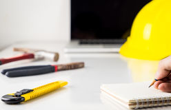 Engineer is taking note on a desk full of construction. Equipment Royalty Free Stock Photography