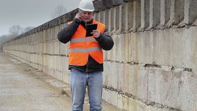 Engineer talking on cell phone the concrete wall stock video footage