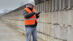 Engineer talking on cell phone the concrete wall stock footage