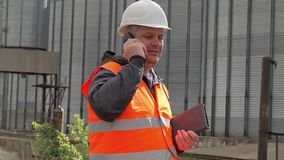 Engineer talking on cell phone at the factory stock footage