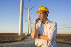 Engineer Talking on Cell Phone in Front of Modern Wind Turbines Stock Photography