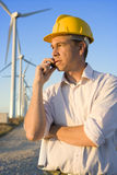 Engineer Talking on Cell Phone in Front of Modern Wind Turbines Royalty Free Stock Photography