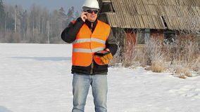 Engineer talking on a cell phone near destroyed building stock footage
