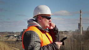 Engineer talking on the cell phone near factory stock footage